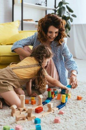 uśmiechnięta niania z dzieckiem bawiąca się wielobarwnymi klockami siedząc na podłodze