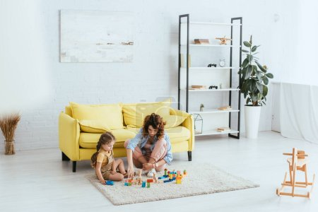 selective focus of babysitter and child playing with multicolored blocks on floor in living room