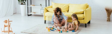 Photo pour Image horizontale de nounou et enfant jouant avec des blocs multicolores sur le sol - image libre de droit