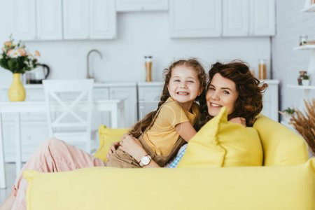 Photo for Cheerful babysitter and child smiling at camera while embracing on sofa in kitchen - Royalty Free Image