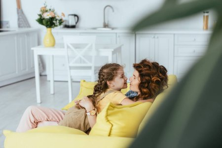 selective focus of cute kid hugging happy nanny sitting on sofa in kitchen