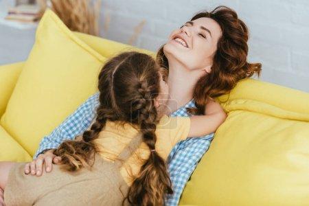 child embracing happy babysitter sitting on sofa with closed eyes