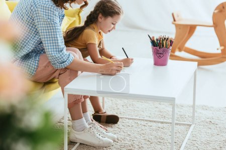 Photo for Cropped view of nanny and child drawing with pencils, selective focus - Royalty Free Image