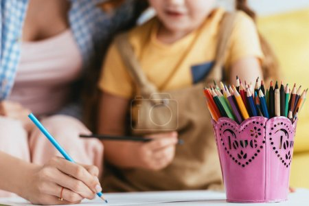 Photo for Selective focus of nanny drawing with pencil near child and pen holder on table - Royalty Free Image