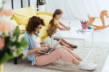 Foto de Enfoque selectivo de la niñera sentada en el suelo y trabajando en el ordenador portátil cerca del dibujo del niño con lápiz - Imagen libre de derechos
