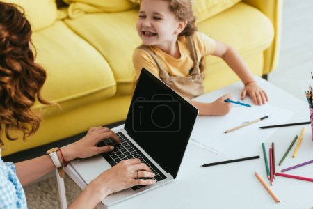 Photo for High angle view of happy child drawing with pencil near nanny using laptop with blank screen - Royalty Free Image