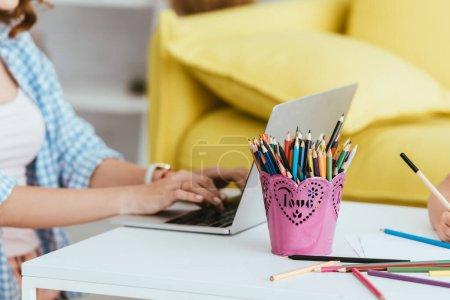 Photo pour Vue recadrée du pigiste à l'aide d'un ordinateur portable sur la table près du porte-stylo avec crayons de couleur et inscription d'amour - image libre de droit