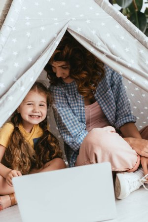 happy babysitter and adorable child sitting in toy wigwam near laptop