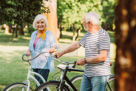 Selective focus of smiling senior woman with bicycle looking at camera near husband in park