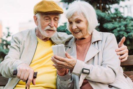 Photo pour Foyer sélectif de sourire femme âgée tenant smartphone près du mari sur le banc dans le parc - image libre de droit