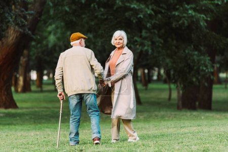 Photo for Senior woman looking at camera while walking with husband in park - Royalty Free Image