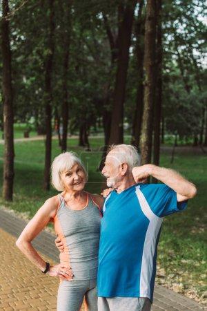 Mujer mayor sonriente abrazando marido en ropa deportiva en el parque