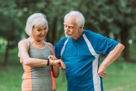 Photo for Smiling senior woman looking at fitness tracker near husband in park - Royalty Free Image