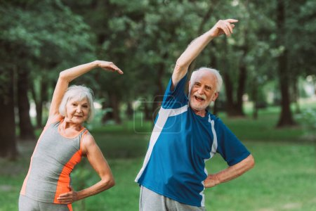 Photo for Cheerful senior couple training and looking at camera in park - Royalty Free Image