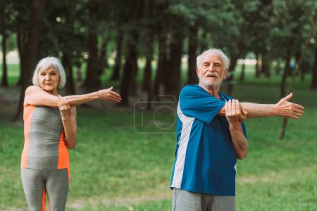 Photo for Selective focus of senior man exercising near wife in park - Royalty Free Image
