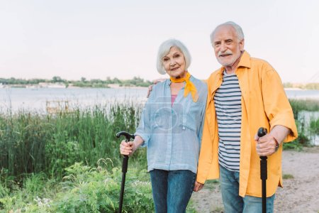 Photo for Smiling senior man embracing wife with walking stick in park - Royalty Free Image