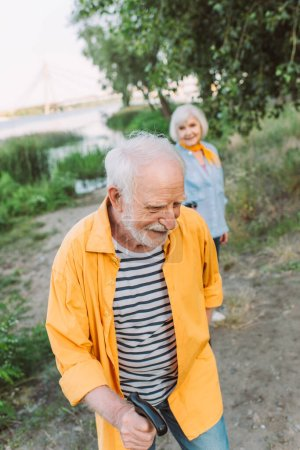 Photo for Selective focus of smiling senior man with walking stick near wife in park - Royalty Free Image