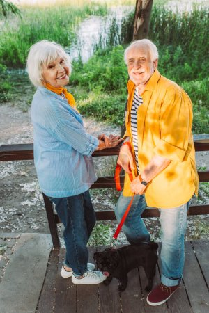 Smiling senior couple with pug dog on leash looking at camera in park