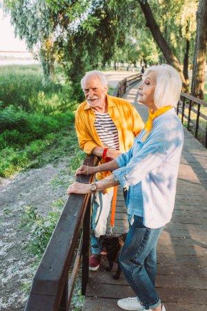 Mujer mayor de pie cerca de marido sonriente con perrito con correa en el puente en el parque