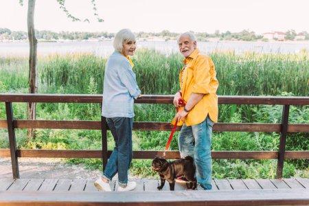 Photo pour Foyer sélectif de sourire couple âgé avec chiot en laisse regardant la caméra sur le pont dans le parc - image libre de droit