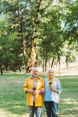 Cheerful elderly couple with paper cups looking at camera in park
