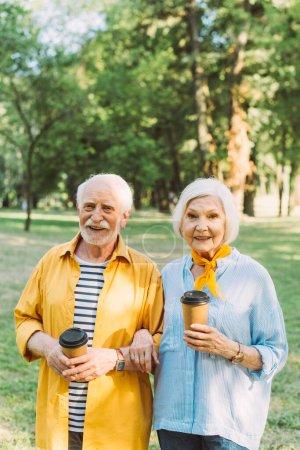 Lächelnde Frau hält Coffee to go in der Hand und lächelt in die Kamera neben ihrem Mann im Park