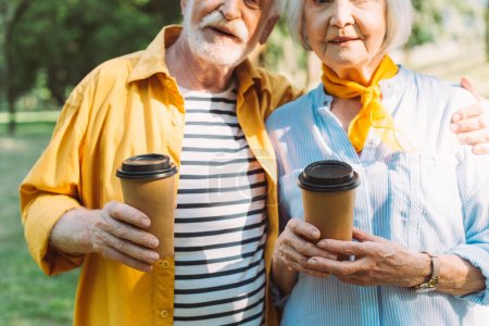 Photo for Cropped view of senior man holding coffee to go and embracing wife in park - Royalty Free Image
