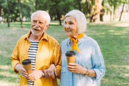 Pareja de ancianos positivos sosteniendo vasos desechables en el parque en verano