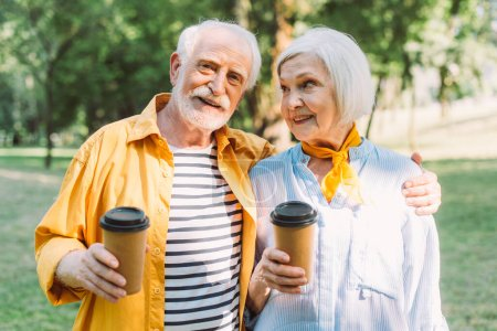 Photo for Smiling elderly man holding coffee to go and hugging wife in park - Royalty Free Image