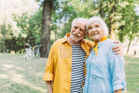 Positive senior man hugging smiling wife in summer park