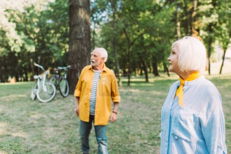 Photo for Selective focus of smiling elderly woman looking away near husband in park - Royalty Free Image