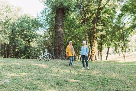 Couple âgé souriant marchant sur la pelouse avec des vélos près de l'arbre dans le parc