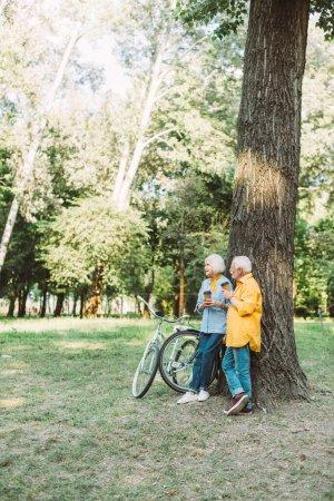 Homme âgé avec tasse en papier regardant femme souriante près de l'arbre et des vélos dans le parc