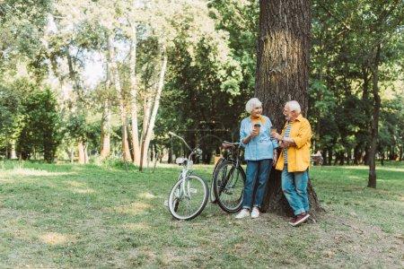 Sonriente hombre sosteniendo la taza de papel y mirando a la esposa mayor al lado del árbol en el parque