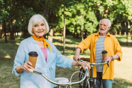 Photo for Selective focus of elderly woman holding paper cup near bike and husband in park - Royalty Free Image