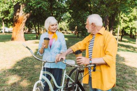 Photo pour Couple aîné souriant avec café à emporter et vélos dans le parc - image libre de droit