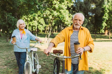 Selective focus of smiling senior man holding paper cup near wife with bike in park