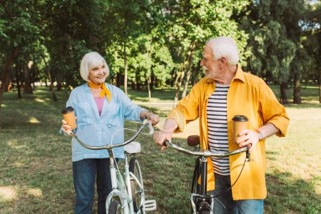 Photo for Cheerful senior man holding coffee to go and looking at wife near bicycle in park - Royalty Free Image