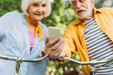 Selective focus of elderly couple using smartphone near bicycles in park