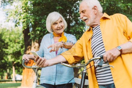 Photo for Selective focus of happy man holding smartphone while wife pointing with finger near bikes in park - Royalty Free Image