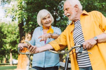 Photo pour Focus sélectif de l'homme heureux tenant smartphone tandis que la femme pointant du doigt près des vélos dans le parc - image libre de droit