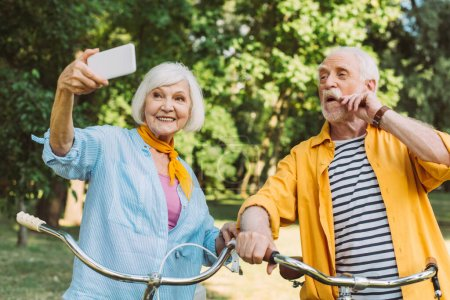 Photo for Senior woman smiling while taking selfie near husband and bicycles in park - Royalty Free Image