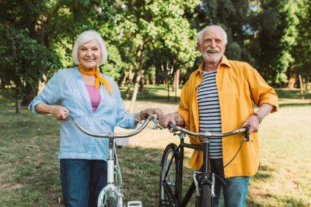 Photo pour Couple âgé positif souriant près des vélos dans le parc d'été - image libre de droit