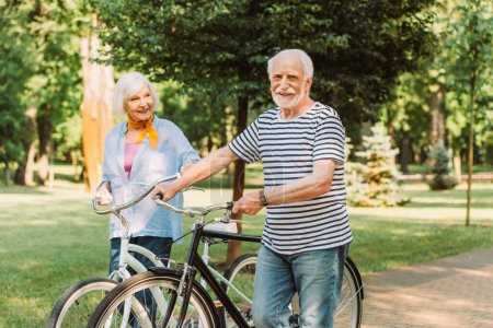 Smiling man looking at camera while walking with bike near wife in park