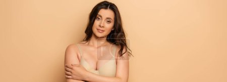 Photo for Panoramic shot of brunette woman in bra looking at camera while standing with crossed arms on beige - Royalty Free Image
