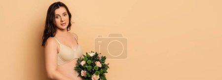Photo pour Image horizontale de la femme enceinte en lingerie tenant bouquet près du ventre tout en regardant la caméra sur beige - image libre de droit