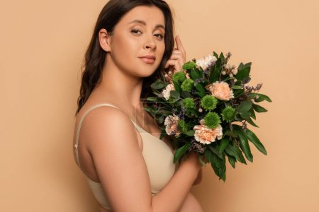 Photo for Young pregnant woman in lingerie touching hair and holding bouquet of fresh flowers on beige - Royalty Free Image