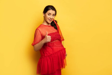 pregnant woman in red tunic showing thumb up while looking at camera on yellow
