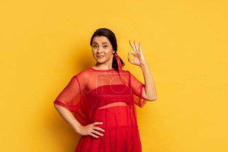 junge schwangere Frau in roter Tunika posiert mit der Hand auf der Hüfte und zeigt ok Geste auf gelb