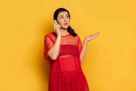 Photo pour Femme enceinte confus en tenue rouge montrant geste haussement d'épaules tout en parlant sur smartphone sur jaune - image libre de droit